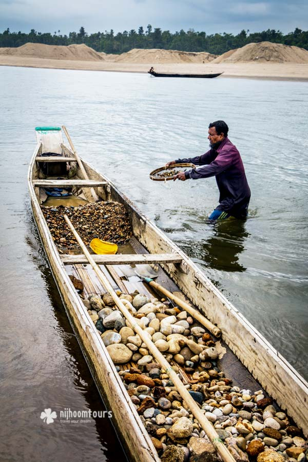 Man collecting stone from river and storing on boat in Jaflong